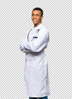 Young afro american man doctor looking over the shoulder with a smile