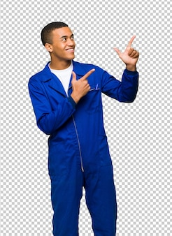 Young afro american worker man pointing with the index finger and looking up