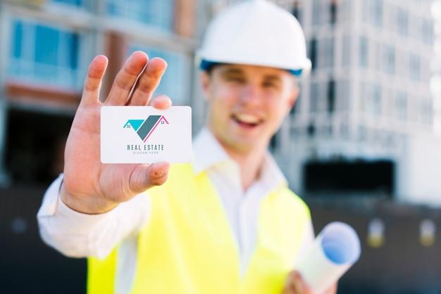 Молодой архитектор держит визитную карточку