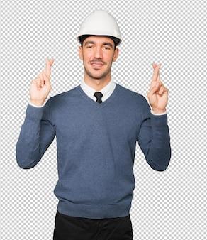 指を交差させたジェスチャーをする若い建築家