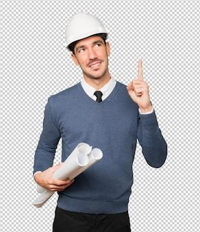 Молодой архитектор делает жест сомнения и указывает пальцем