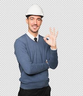 彼の手で大丈夫なジェスチャーをする若い建築家