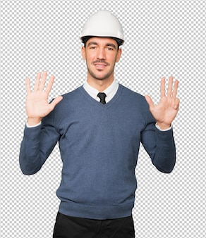 Young architect making a gesture of number nine