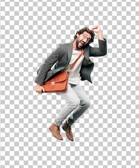 Молодой бородатый бизнесмен носить блейзер и прыгать. успех или победа