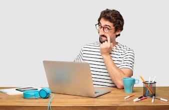 Young bearded graphic designer with a laptop looking, observing, keeping an eye on an object