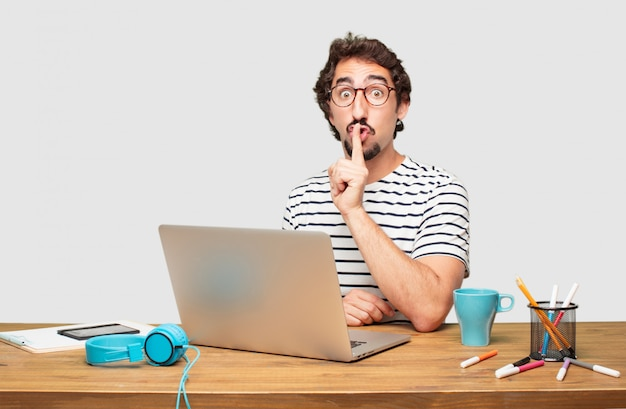 Young bearded graphic designer with a laptop gesturing