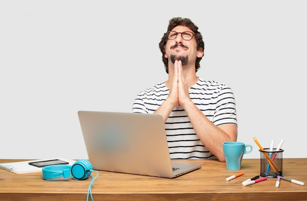 Young bearded graphic designer with a laptop praying in a saintly manner