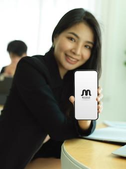 Young beautiful female holding smartphone mockup