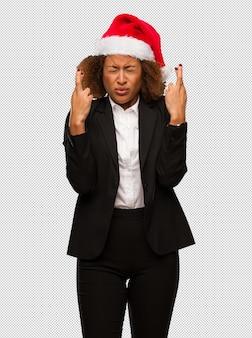 Молодой черный бизнесмен, носить рождественские санта шляпу, пересекая пальцы для удачи