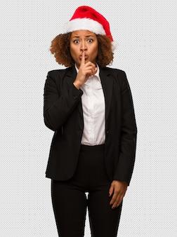 秘密を保つか、沈黙を求めるクリスマスサンタの帽子を身に着けている若い黒の実業家