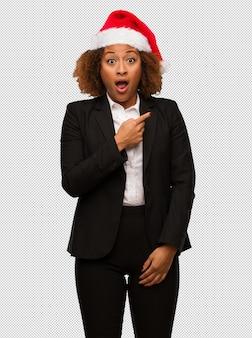 측면을 가리키는 크리스마스 산타 모자를 쓰고 젊은 흑인 사업가