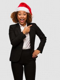 웃 고 측면을 가리키는 크리스마스 산타 모자를 쓰고 젊은 흑인 사업가