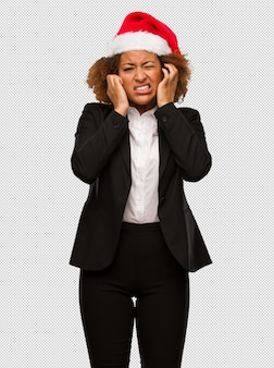 Young black businesswoman wearing a christmas santa hat covering ears with hands
