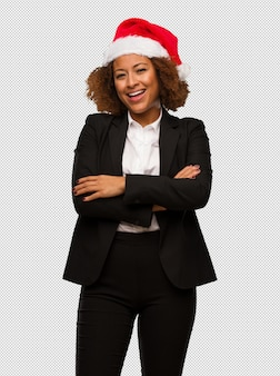 Young black businesswoman wearing a christmas santa hat crossing arms, smiling and relaxed