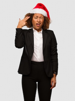 Young black businesswoman wearing a christmas santa hat doing a suicide gesture