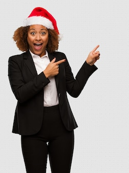 Young black businesswoman wearing a christmas santa hat holding something with hand