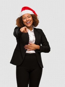 Young black businesswoman wearing a christmas santa hat laughing and pointing