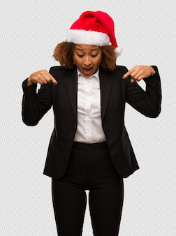 Young black businesswoman wearing a christmas santa hat pointing down