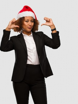 Young black businesswoman wearing a christmas santa hat pointing fingers, example to follow
