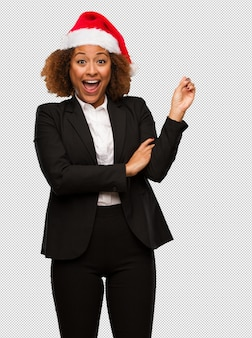 Young black businesswoman wearing a christmas santa hat pointing to the side with finger