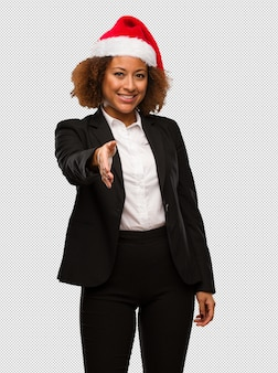 Young black businesswoman wearing a christmas santa hat reaching out to greet someone