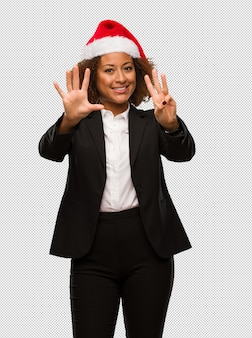 Young black businesswoman wearing a christmas santa hat showing number eight