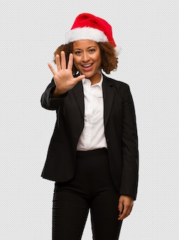 Young black businesswoman wearing a christmas santa hat showing number five