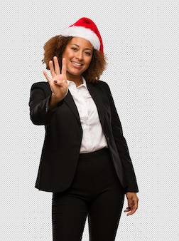 Young black businesswoman wearing a christmas santa hat showing number four