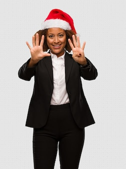 Young black businesswoman wearing a christmas santa hat showing number nine