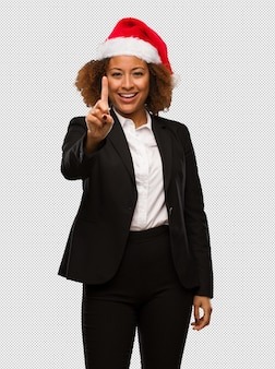 Young black businesswoman wearing a christmas santa hat showing number one