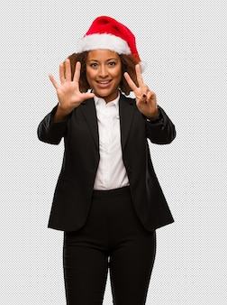 Young black businesswoman wearing a christmas santa hat showing number seven