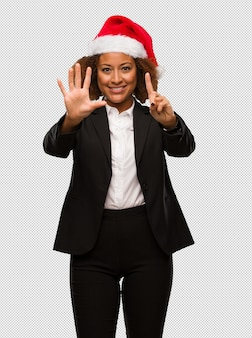 Young black businesswoman wearing a christmas santa hat showing number six