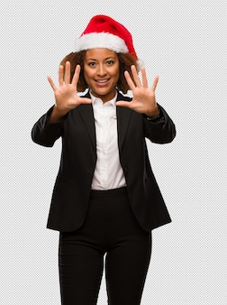 Young black businesswoman wearing a christmas santa hat showing number ten