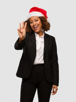 Young black businesswoman wearing a christmas santa hat showing number three