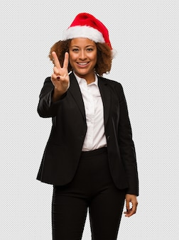 Young black businesswoman wearing a christmas santa hat showing number two