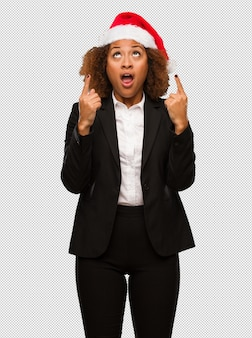 Young black businesswoman wearing a christmas santa hat surprised pointing up to show something