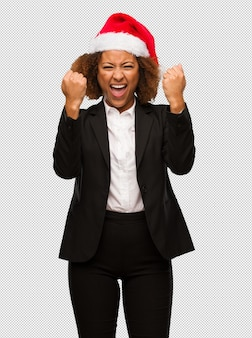 Young black businesswoman wearing a christmas santa hat surprised and shocked