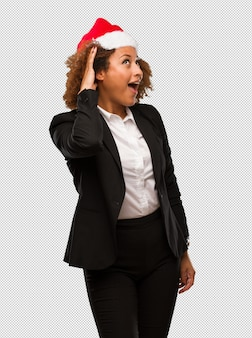 Young black businesswoman wearing a christmas santa hat try to listening a gossip