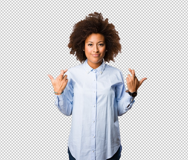 Young black woman doing good luck gesture