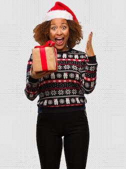 승리 또는 성공을 축하하는 크리스마스에 선물을 들고 젊은 흑인 여성