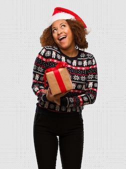 Молодая черная женщина, держащая подарок в день рождества, мечтая о достижении целей и задач