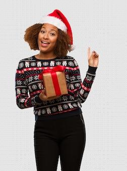 손가락으로 측면을 가리키는 크리스마스 날에 선물을 들고 젊은 흑인 여성