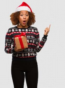 크리스마스 날 측면을 가리키는 선물을 들고 젊은 흑인 여성