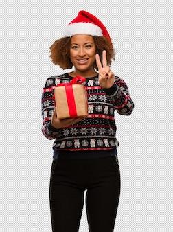 Молодая чернокожая женщина с подарком в день рождества, показывая номер два