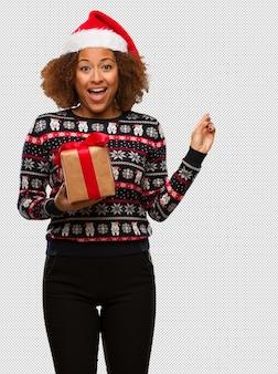 크리스마스 날에 선물을 들고 웃 고 측면을 가리키는 젊은 흑인 여성