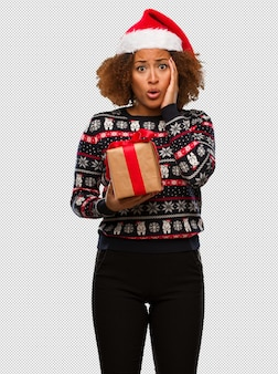 크리스마스 날에 선물을 들고 젊은 흑인 여성이 놀라서 충격을