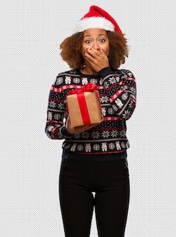 크리스마스에 선물을 들고 젊은 흑인 여성이 매우 무서워하고 두려워 숨겨진
