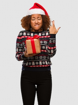 Young black woman holding a gift in christmas day crossing fingers for having luck
