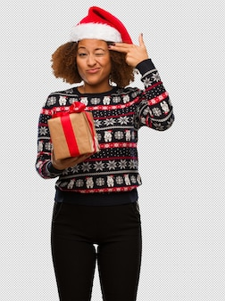 Young black woman holding a gift in christmas day doing a suicide gesture