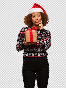 Young black woman holding a gift in christmas day doubting and confused